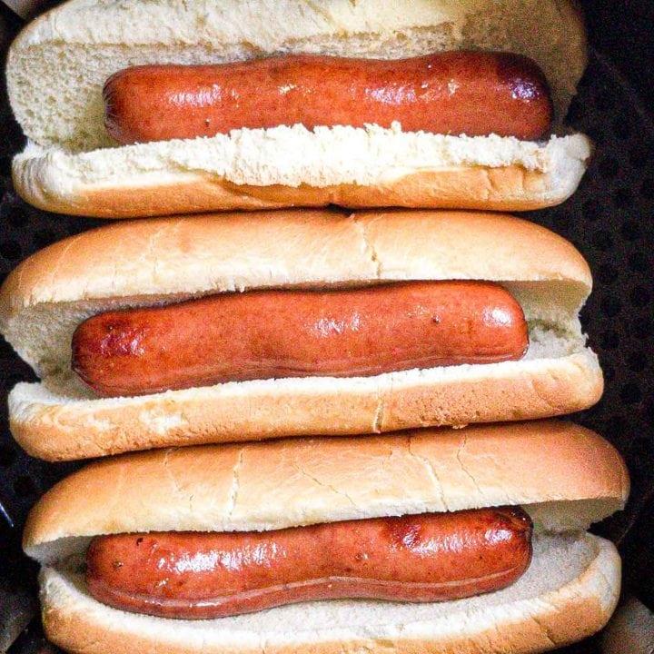 three air fryer hot dogs in an air fryer basket.