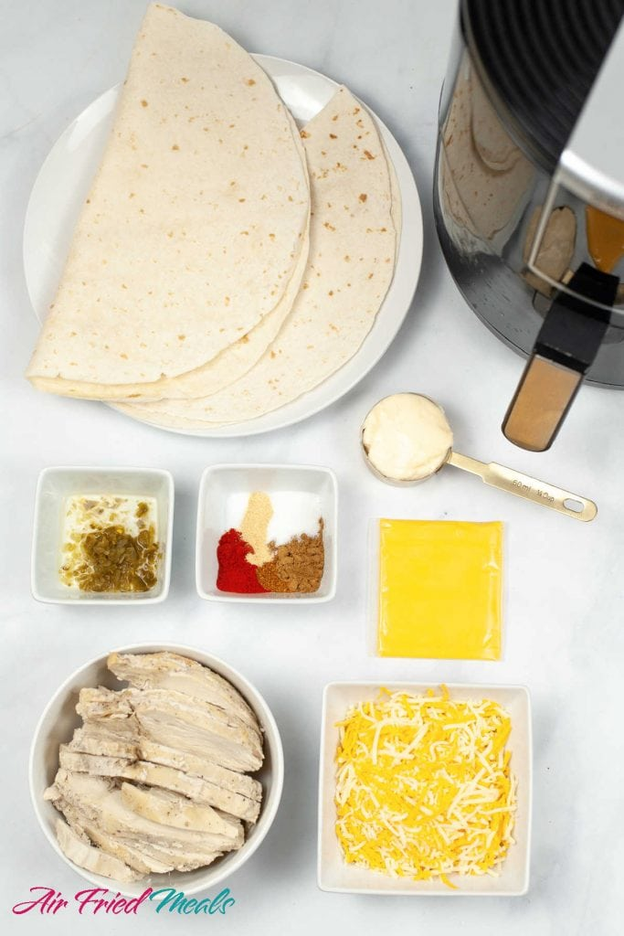 plate with tortillas, measure cup with mayonaise, two white bowls - one with jalapenos and the other with spices, package of American cheese, bowl with sliced roasted chicken, square bowl with shredded cheese.