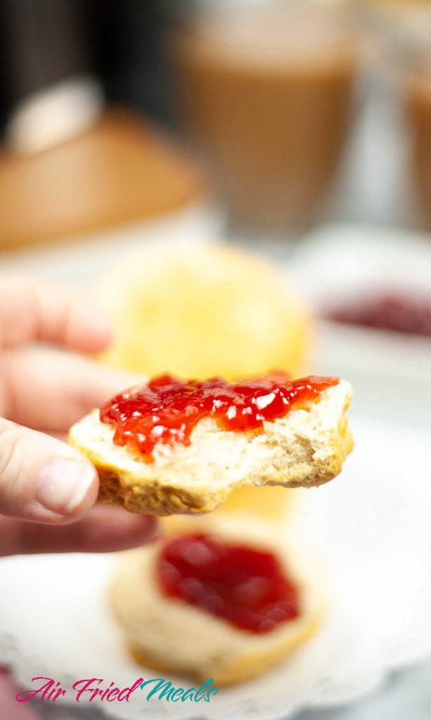 half a biscuit being held up with jam on it, other half of biscuit blurry in background.