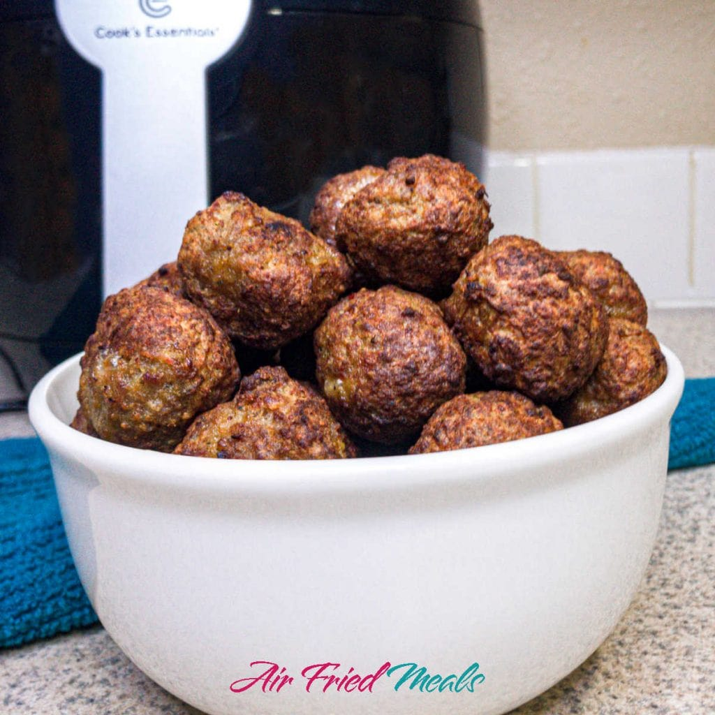 Cooked meatballs in a white bowl.
