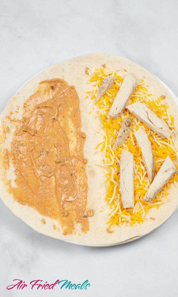 tortilla: left half has sauce covering it, right half has shredded cheese and chicken.