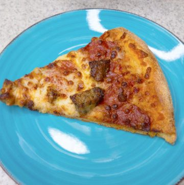 piece of pizza on a teal plate.