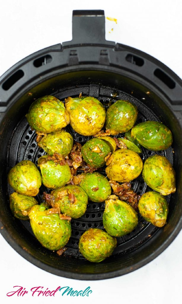 Top down into air fryer basket.  Brussel sprouts with oil and seasoning on them and bacon crumbles around and on top of the Brussel sprouts.
