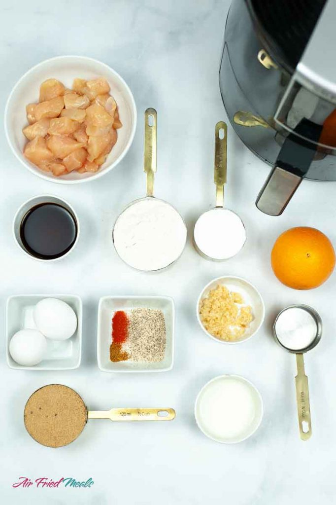 top left has a bowl of raw cut up chicken, part of an air fryer, next row has from left to right, small bowl of soy sauce, measuring cup of flour, measuring cup of corn starch, an orange, next row has a small bowl with two eggs, small bowl with spices, small bowl with minced garlic, measuring cup with vinegar, next row has a measuring cup with brown sugar, and a small bowl of water mixed with corn starch.