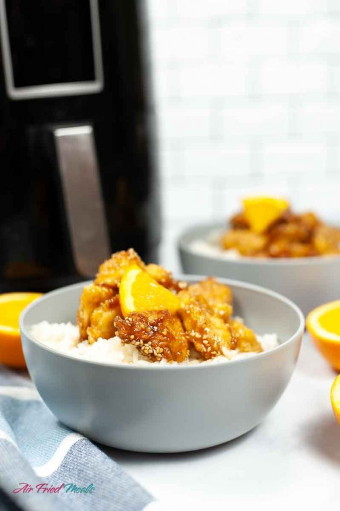 gray bowl with rice and orange chicken in it.
