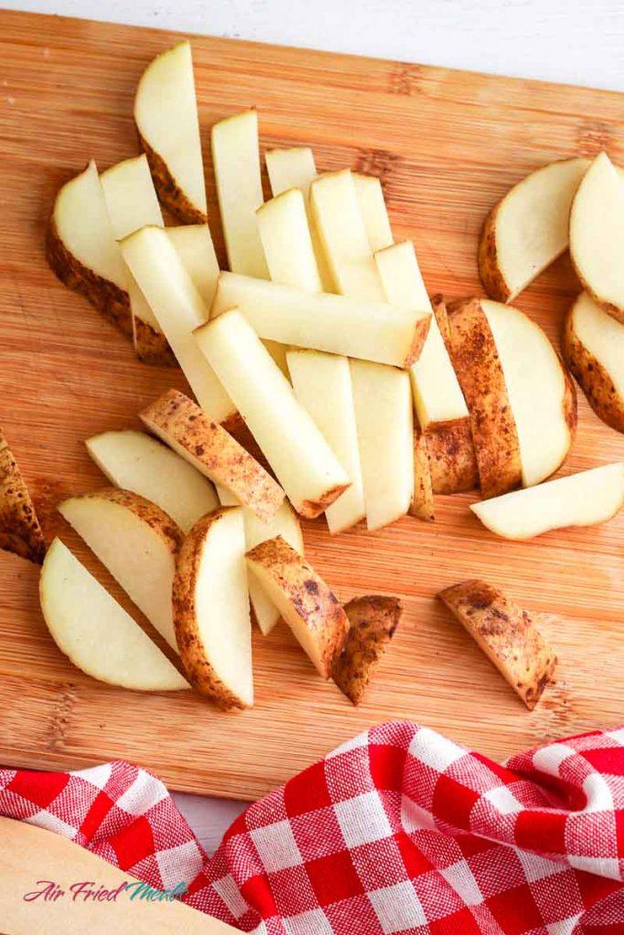 raw potatoes on a cutting board.