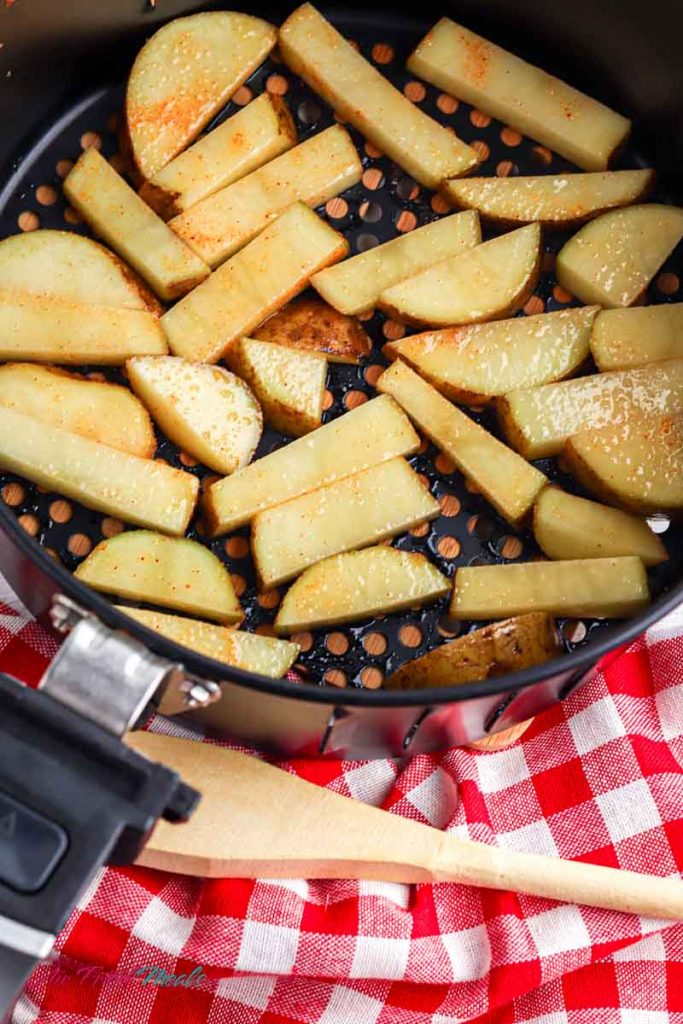 raw potatoes in a single layer in an air fryer basket.