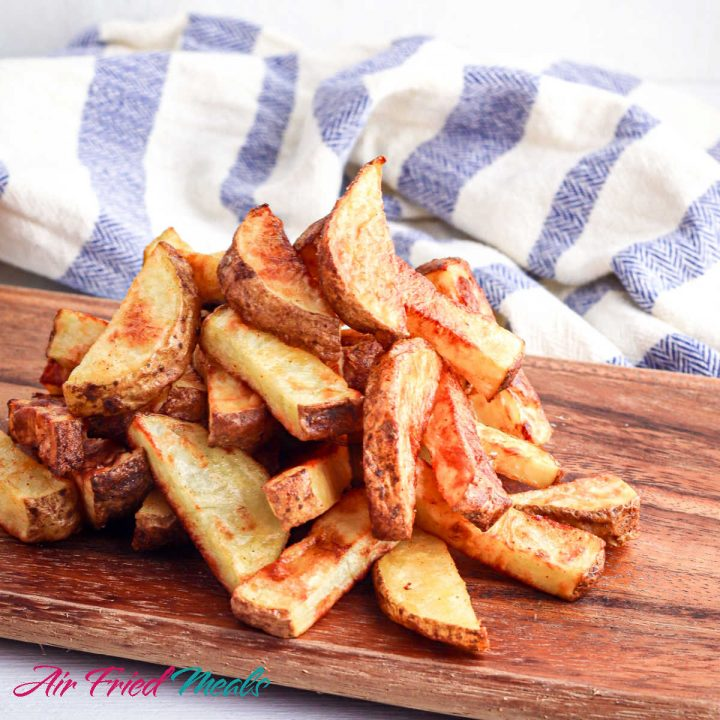 cooked air fryer potato wedges on a cutting board with a blue and white towel behind.