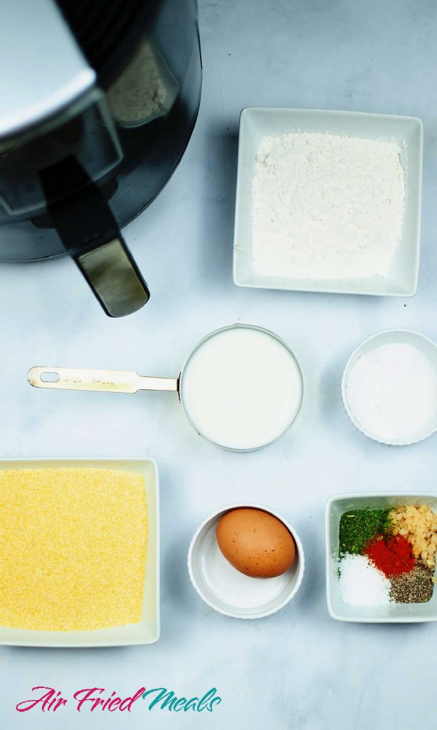 Hush puppies ingredients from top right counter clockwise - bowl of flour, small bowl of baking powder, small bowl of seasonings, 1 egg in a bowl, cornmeal in a bowl, measuring cup of milk.