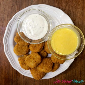 Top down view of a white plate with cooked chicken nuggets and a small bowl of ranch and a small bowl of honey mustard on plate as well.