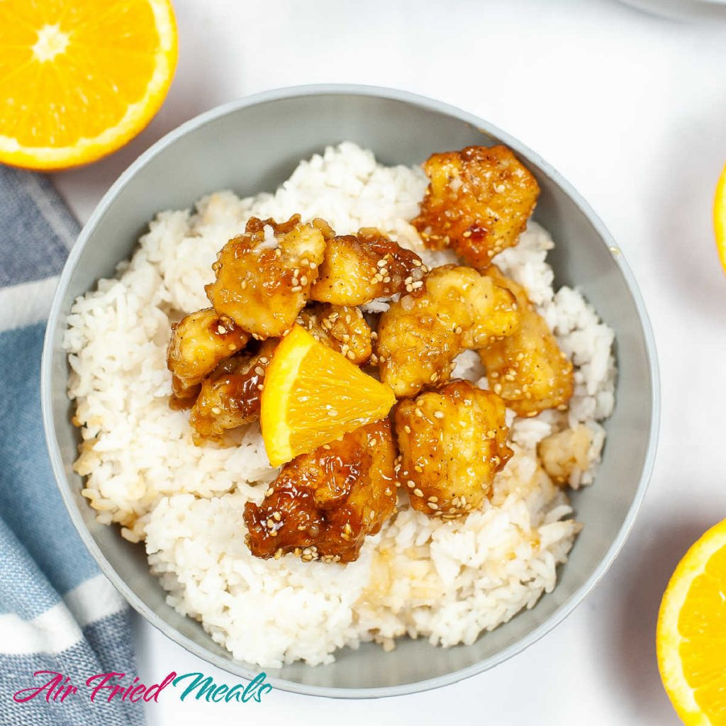 top down view of a grayish bowl with rice, orange chicken, and a piece of orange.