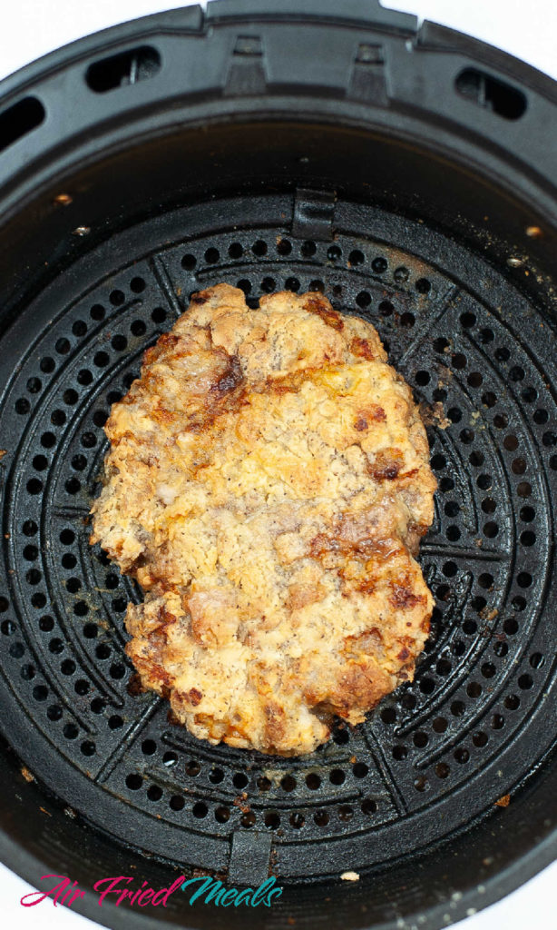Cooked chicken fried steak in an air fryer basket.