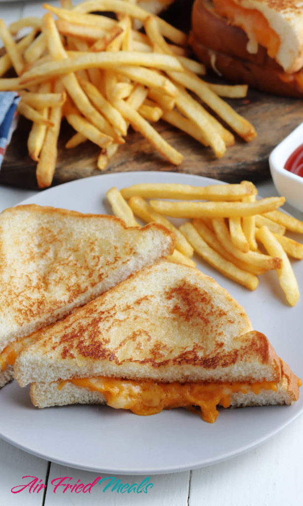 Grilled cheese sandwich on a plate with some fries.