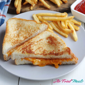 Two halves of a grilled cheese sandwich on a white plate with fries.