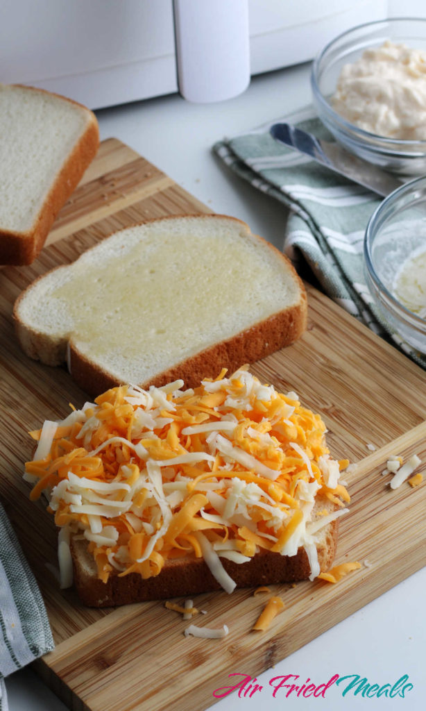 two slices of bread with one piled with grated cheese.