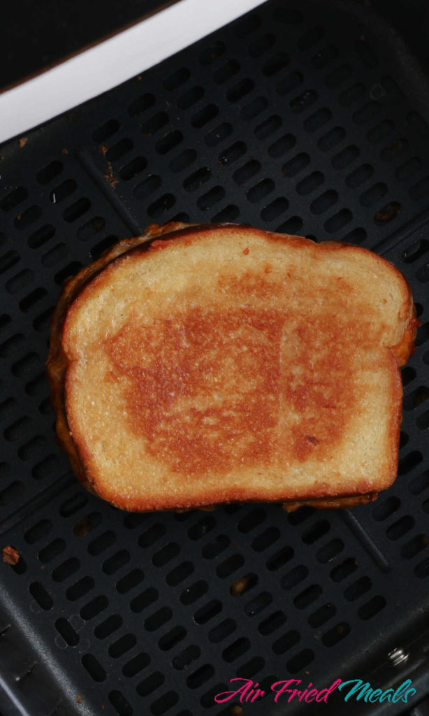Cooked grilled cheese sandwich in air fryer drawer.