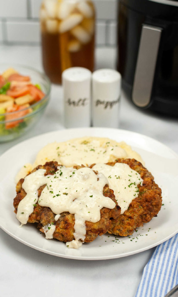 Plate with chicken fried steak cooked, mashed potatoes behind it and gravy over the top of both.