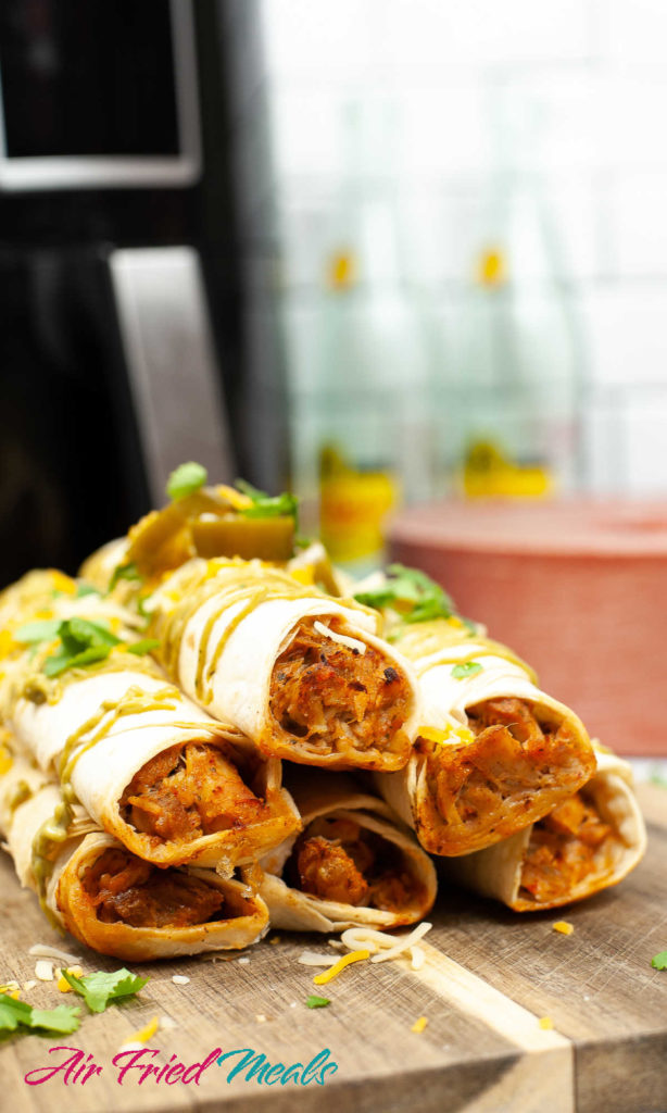 Cooked chicken taquitos stacked on cutting board.