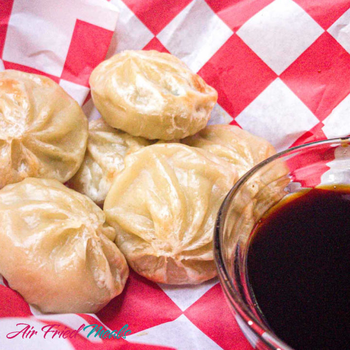 Frozen dumplings cooked in the air fryer on a red and white checkered paper with a small dipping container of soy sauce.