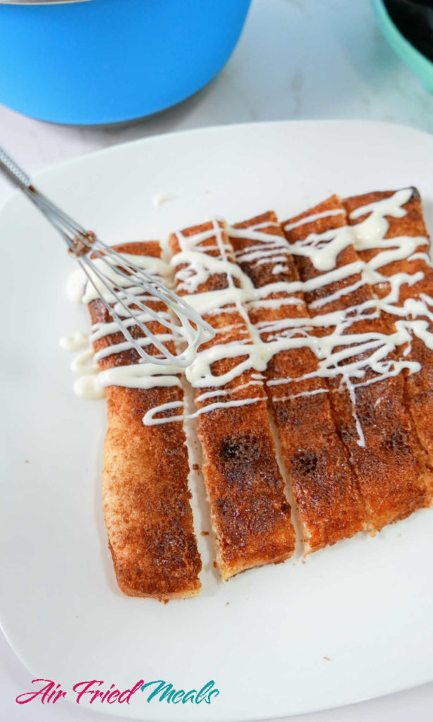 frosting being drizzled over cinnamon sticks.