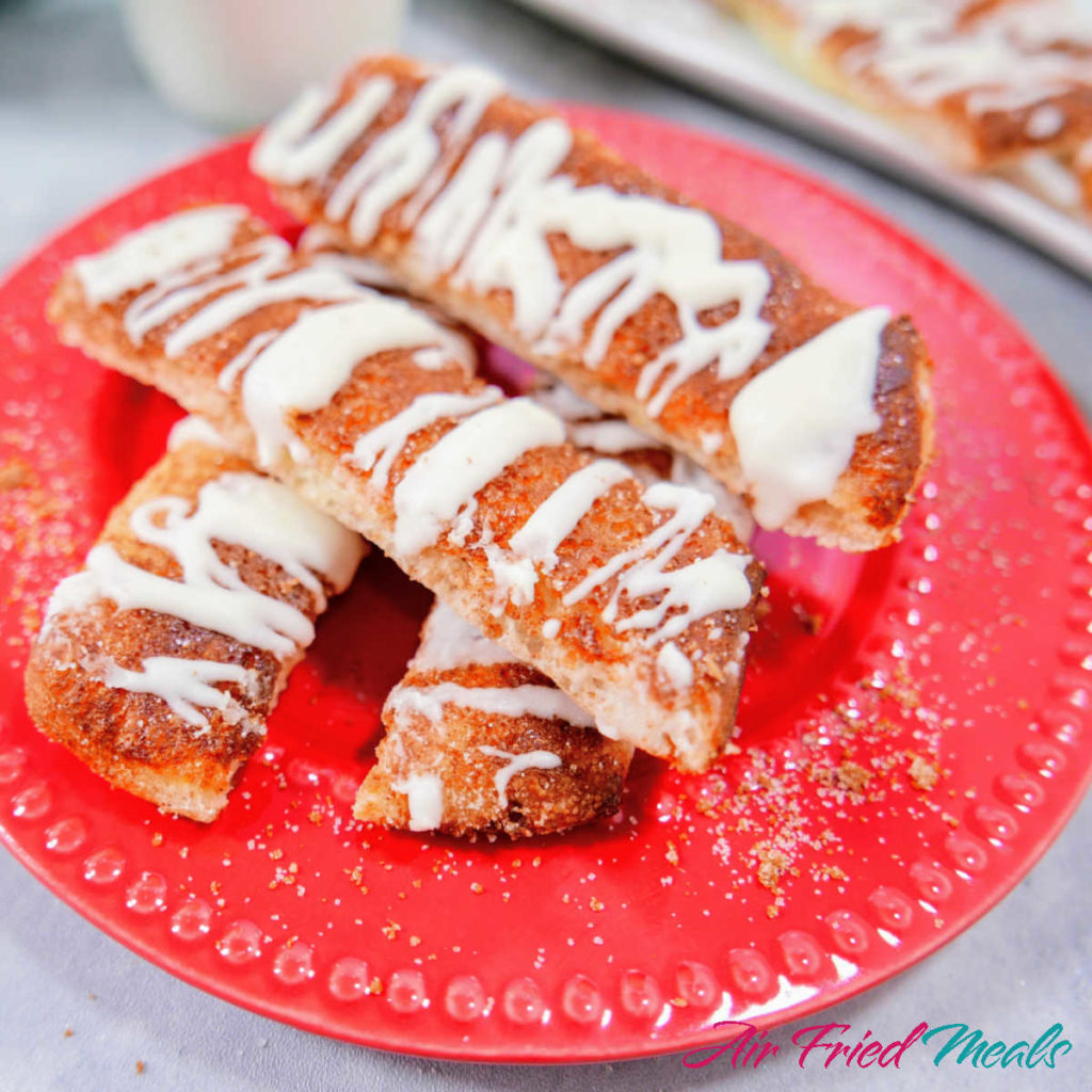 Cinnamon sticks stacked on red plate.