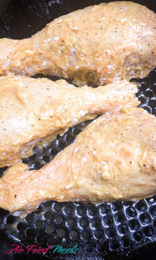 Breaded chicken in air fryer basket, covered in oil.