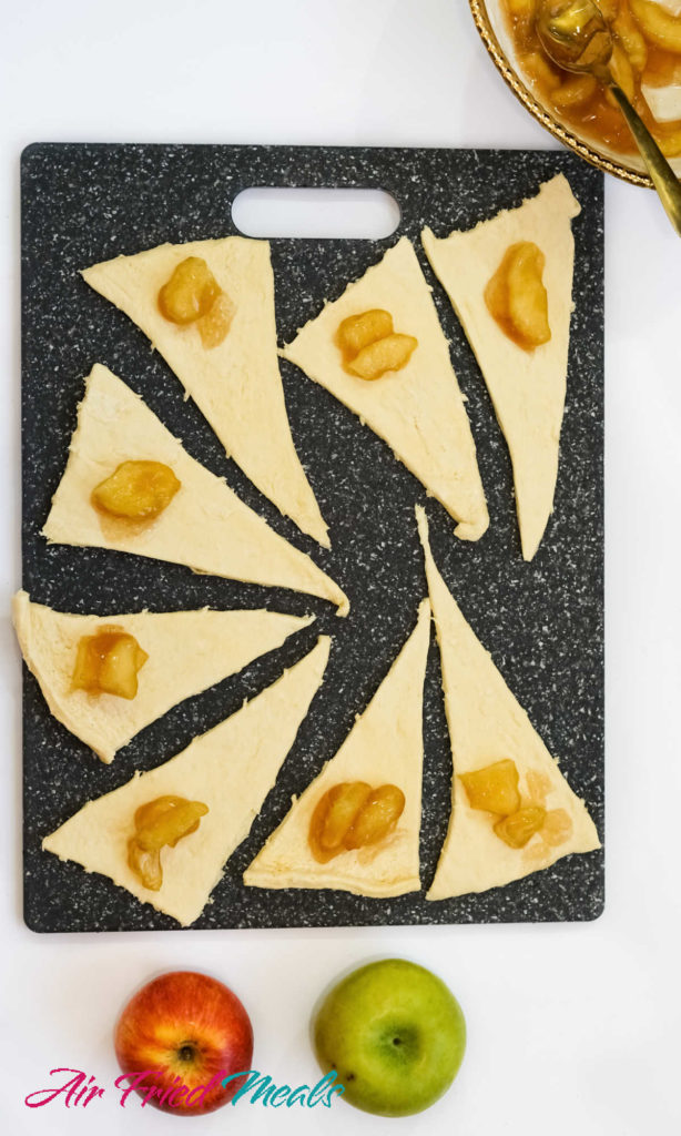 Crescent Rolls open on cutting board with apple pie filling on each one.