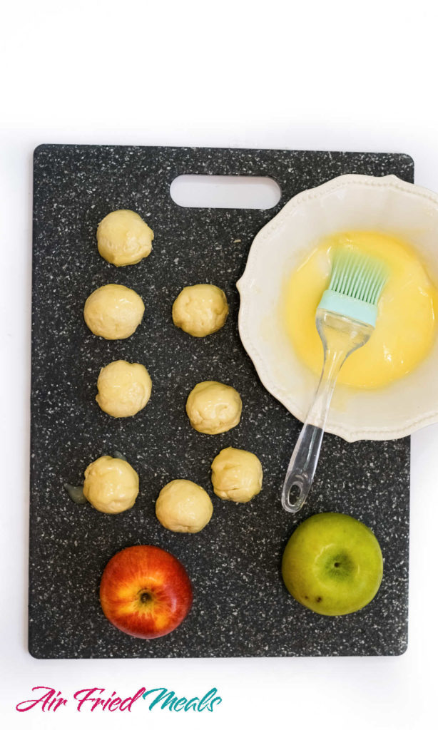 Uncooked donut holes on cutting board with melted butter next to them.