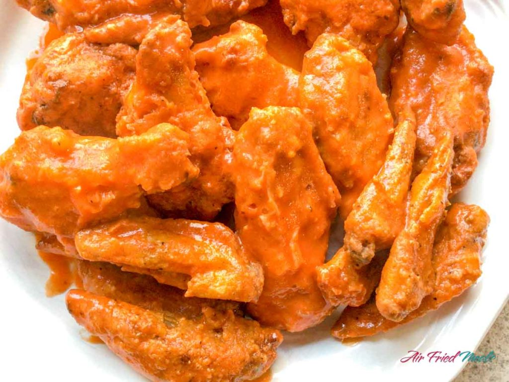 Closeup of cooked chicken wings that are sauced.