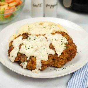 chicken fried steak with mashed potatoes behind it.