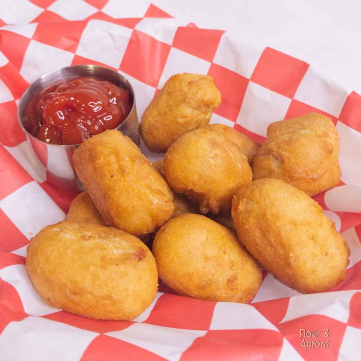 Air Fryer mini corn dogs in basket with small container of ketchup.