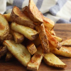 pile of potato wedges on cutting board.