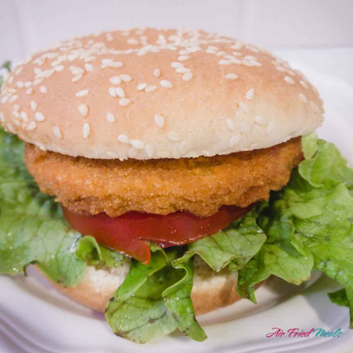 Side view of a chicken sandwich with lettuce and tomato.
