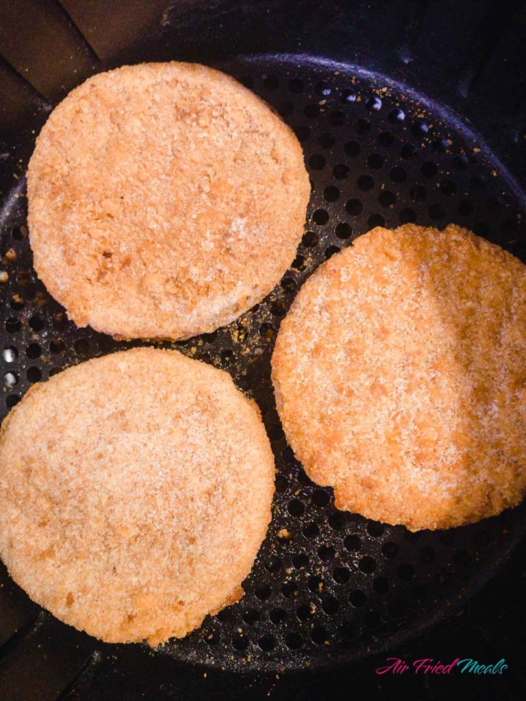 Three chicken patties in an air fryer basket.