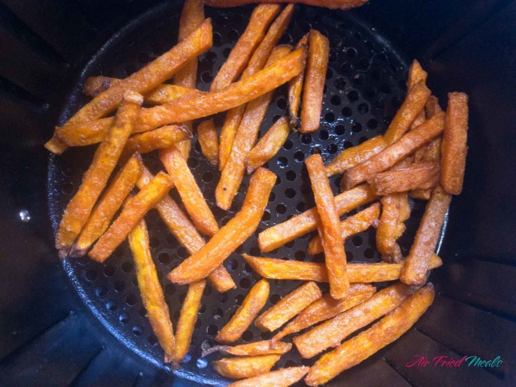 Sweet potato fries in air fryer basket.