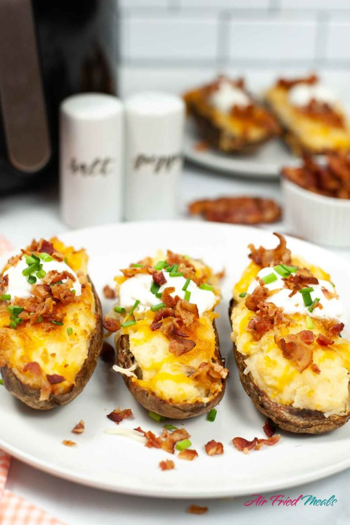 Three twice baked potatoes with all the toppings on a plate.