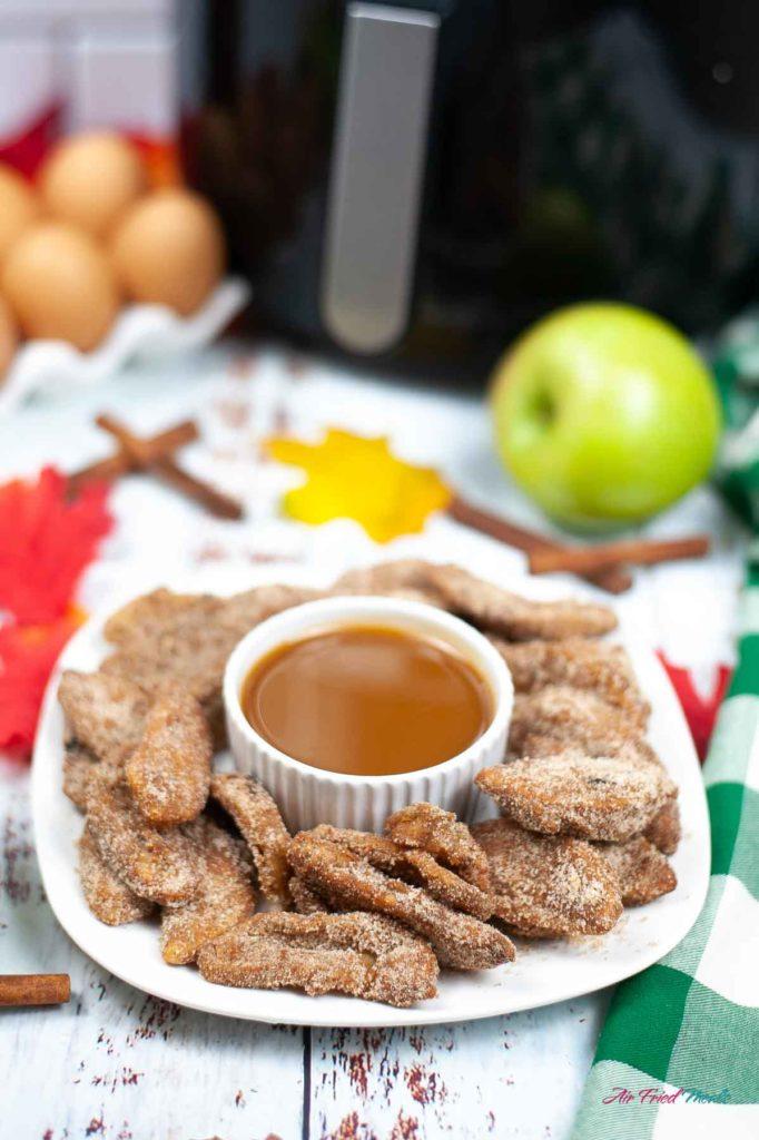 Apple fries surrounding caramel sauce on a plate.