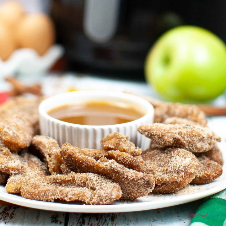 Air Fryer Apple Fries around a container of caramel sauce on a plate.