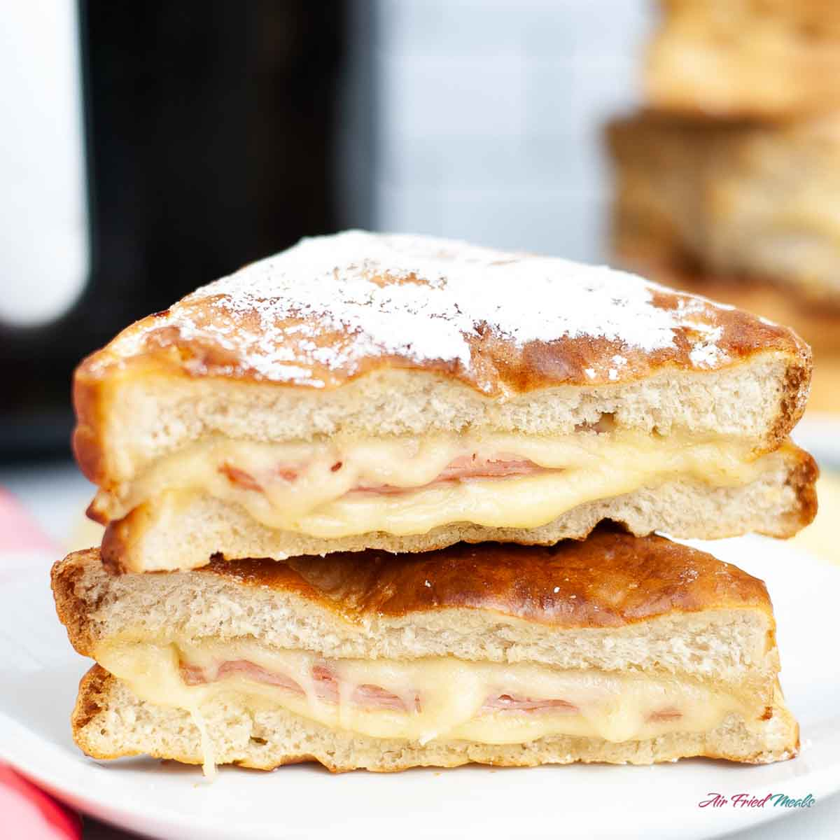 Stacked Monte Cristo sandwiches with a dusting of powdered sugar.