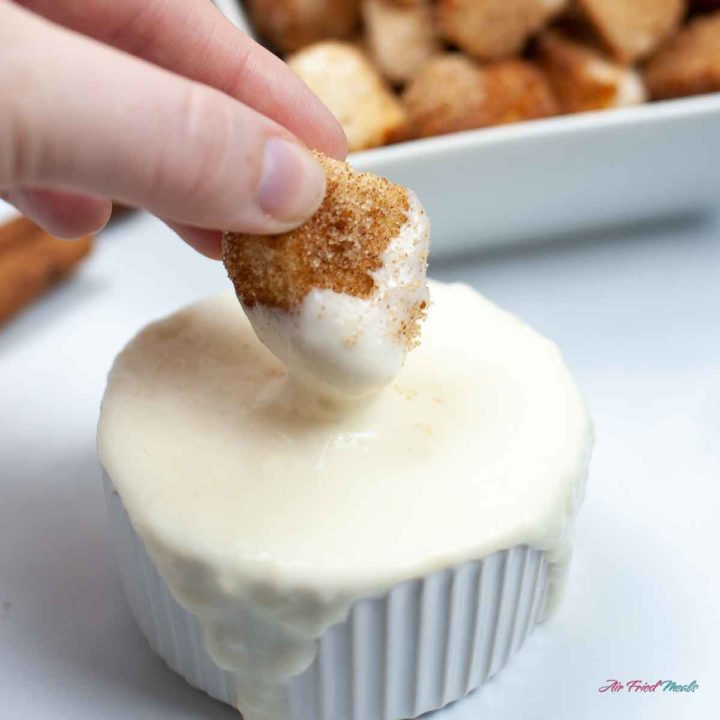 Churro Bites being dipped in cream cheese dip.